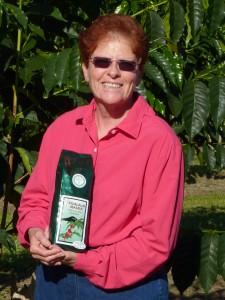 Marian wearing her Coolibar Everyday Blouse holding Hualalai Mauka coffee